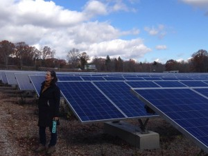 Jenny Isler stands in front of solar panels at SolarFlair