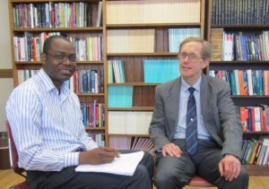 Clark University Ph.D. student Gbeton B. Somasse, left, meets with his adviser, Professor of Economics Wayne Gray.