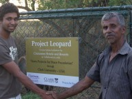 Sanjiv Fernando '15 (left) shakes hands with W.P. Piyadasa, a cattle herder who received one of the mesh enclosures.