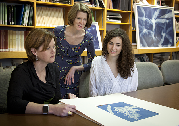 (L. to r.) Nancy Burns, Worcester Art Museum assistant curator of prints, drawings and photographs, Associate Professor Kristina Wilson and Hannah Jaffe '16 examine an 1854 cyanotype that is in the show.